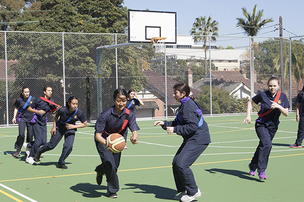 Students playing basketball in recreation space